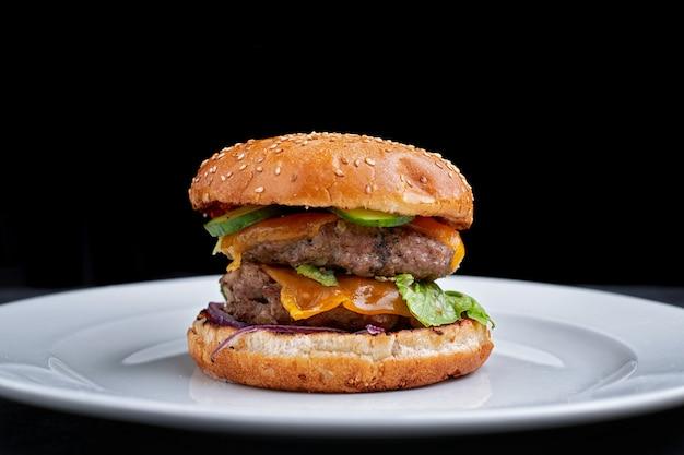 Burger avec double escalope de viande, fromage. concombre et laitue, sur une plaque blanche, sur fond noir