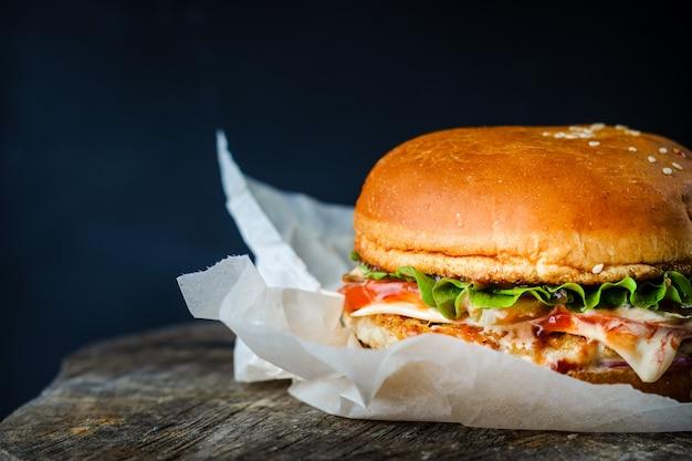 Burger enveloppé dans du papier sur une table en bois sur fond sombre