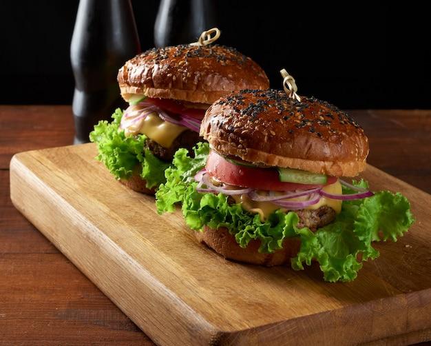 Burger avec escalope de boeuf frite et oignons pain de farine de blé blanc croustillant aux graines de sésame