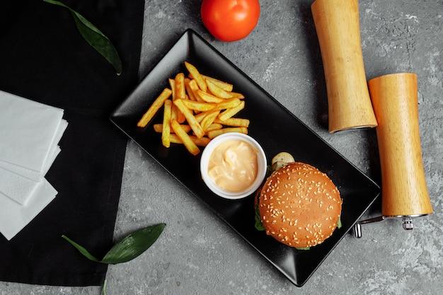 Burger avec escalope, fromage et tomates. avec frites et sauce burger