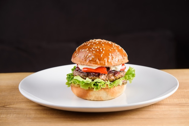 Burger avec escalope, sauce, tomate, laitue, sésame sur plaque blanche sur fond sombre