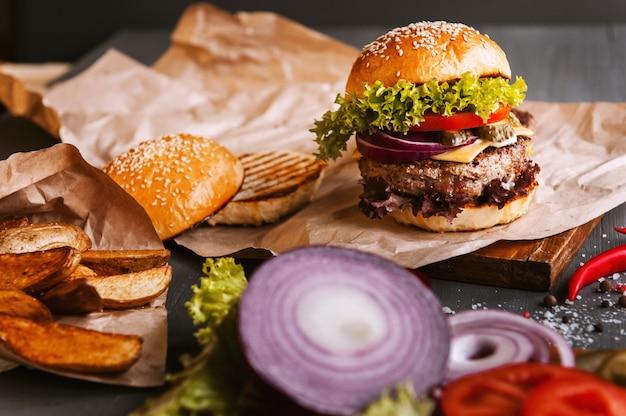 Burger fait maison délicieux sur une table en bois. à côté du composant à hamburger, plateaux en bois, pommes de terre frites et piment.