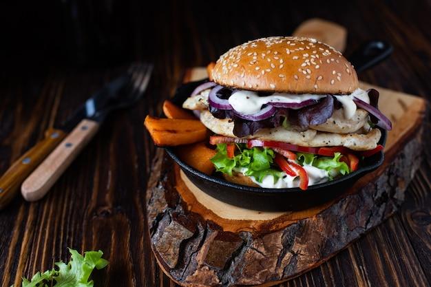 Burger avec filet de poulet grillé, paprika, patate douce, laitue, oignons et yogourt grec