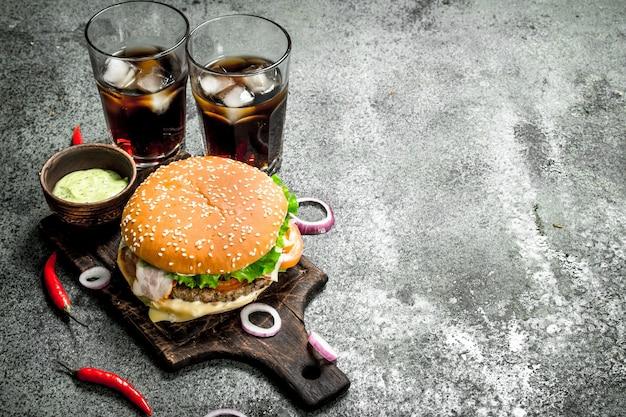 Burger frais avec cola et sauce piquante. sur un fond rustique.