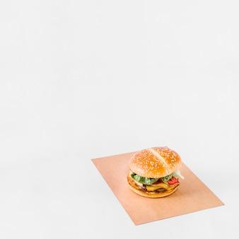 Burger frais sur du papier brun sur fond blanc