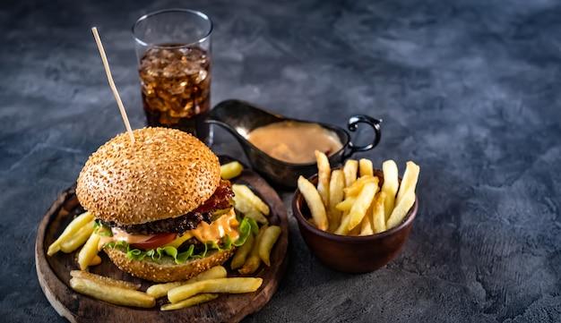 Burger frais avec des frites croustillantes près de boissons et saucières
