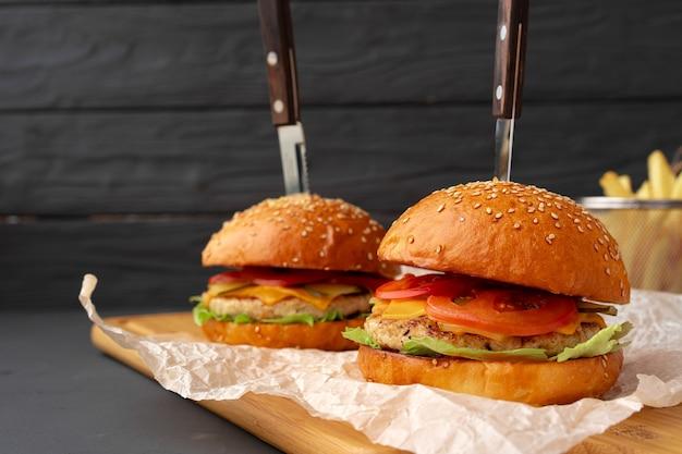 Burger frais et frites sur fond de bois noir