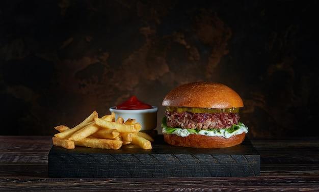 Burger frais avec frites sur planche de bois foncé et bol de sauce tomate