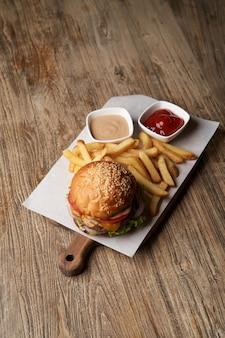 Burger frais et frites sur une planche à découper en bois. restauration rapide, malbouffe