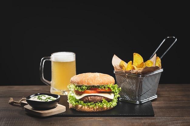 Burger avec frites et bière sur base en bois sur fond noir