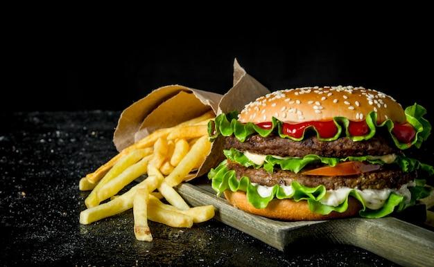 Burger avec frites sur la planche à découper. sur fond rustique noir