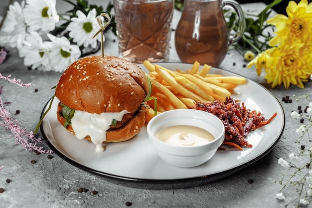 Burger avec frites et sauce sur une plaque blanche