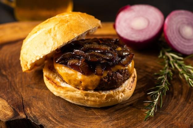Burger gastronomique de viande de ferme biologique avec du pain grillé et croquant, fondant du fromage sur une table en bois