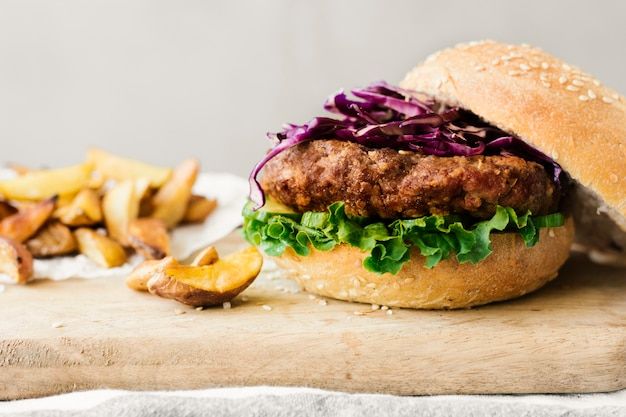Burger gros plan angle avec frites sur planche de bois