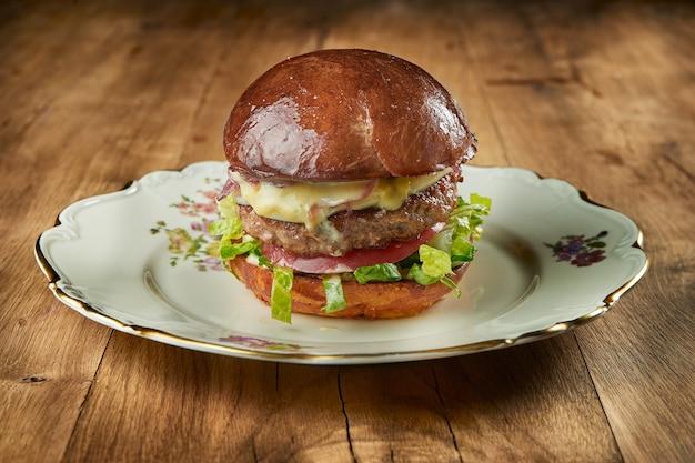 Burger juteux et appétissant avec du boeuf, de la laitue, de la mozzarella et des tomates sur une assiette vintage sur une table en bois. gros plan, mise au point sélective. grain de bruit ajouté sur le poteau