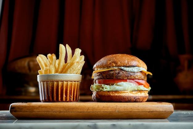 Burger juteux et appétissant avec tomates, laitue, concombre, fromage fondu et oignons avec pain brioché servi sur une planche de bois avec frites