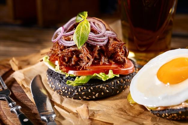Burger juteux sur la planche, fond noir. fond sombre, restauration rapide. cuisine américaine traditionnelle. espace de copie.