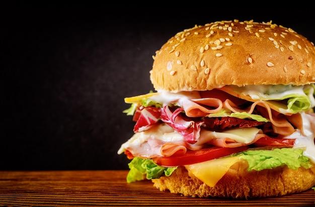 Burger avec laitue, fromage, jambon et tomate sur fond sombre.
