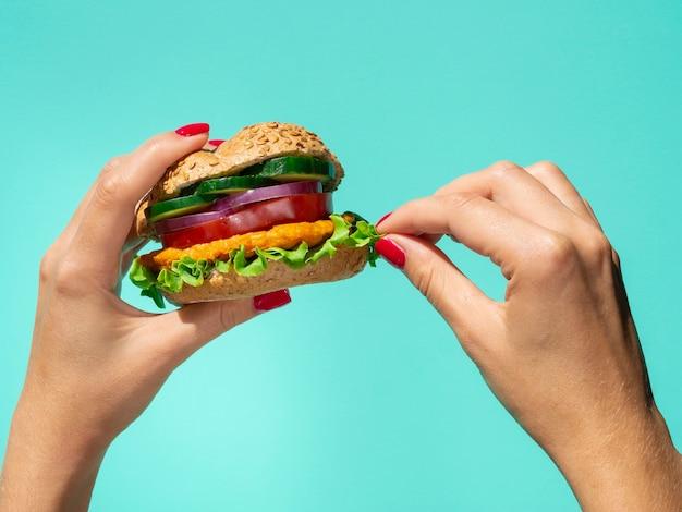 Burger de légumes tenu dans la main sur un fond bleu