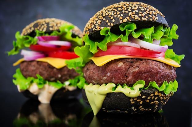 Burger à la main sur une surface sombre. délicieux burger noir