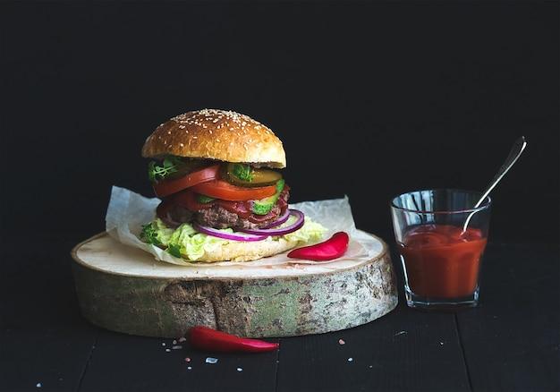 Burger maison fraîche sur une planche de service en bois avec sauce tomate épicée, sel de mer et herbes sur fond noir.