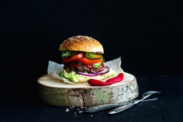 Burger maison fraîche sur une planche de service en bois avec sauce tomate épicée, sel de mer et herbes
