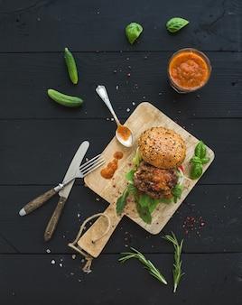 Burger maison fraîche sur une planche de service sombre avec sauce tomate épicée, sel de mer et herbes