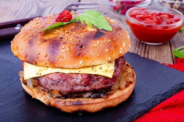 Burger maison avec pain au sésame et boeuf haché sur pierre noire.