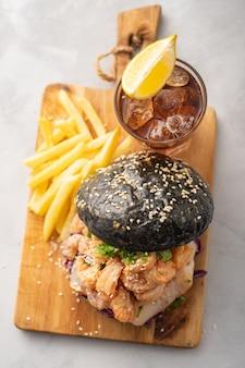 Burger noir aux poissons et crevettes, fishburger aux crevettes roses, vue de dessus.