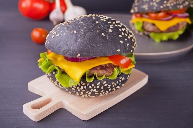 Burger noir fait maison avec une côtelette et des légumes sur la table de cuisson