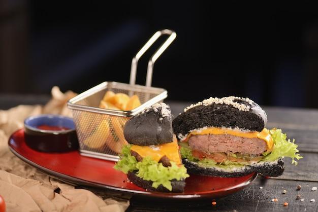 Burger noir avec frites et sauce. dans une assiette rouge sur une table en bois