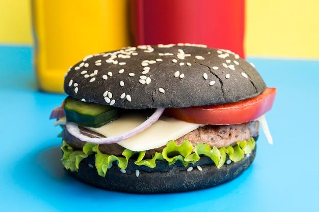 Burger noir sur une table bleue avec des bouteilles derrière