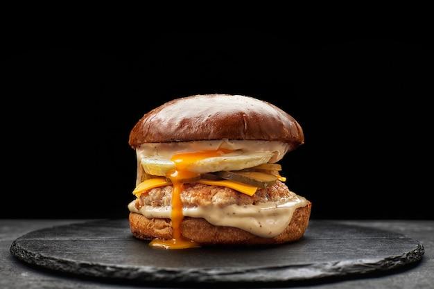 Burger avec oeuf, escalope de viande et fromage sur fond noir