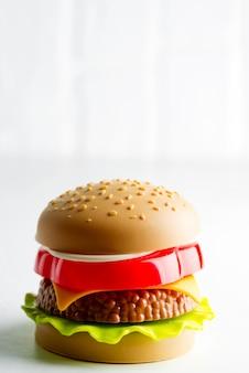 Burger en plastique artificiel avec escalope de viande, tranche de tomates et salade verte sur fond gris clair.