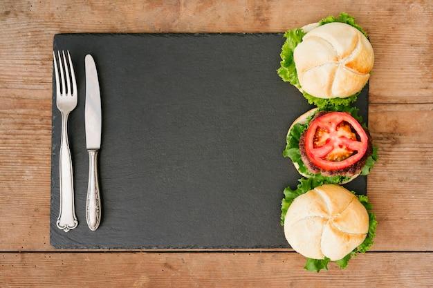 Burger à plat sur ardoise avec couverts