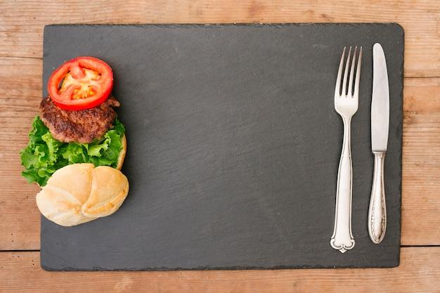 Burger à plat sur ardoise avec fond