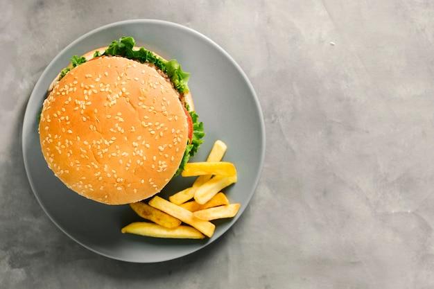 Burger à plat et frites sur assiette avec fond