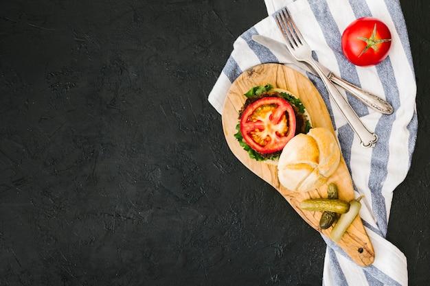 Burger à plat et frites sur une planche en bois avec fond