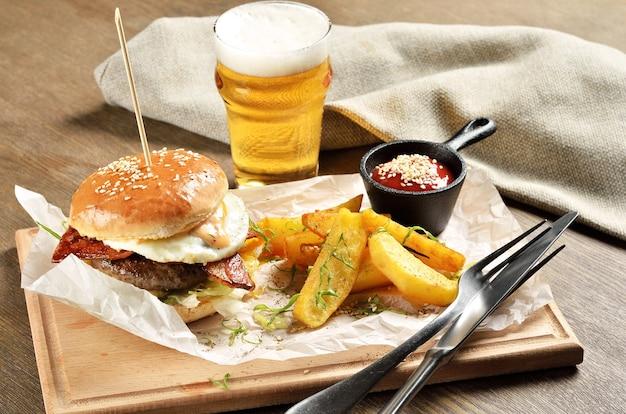 Burger, pommes de terre mexicaines et ketchup sur planche de bois
