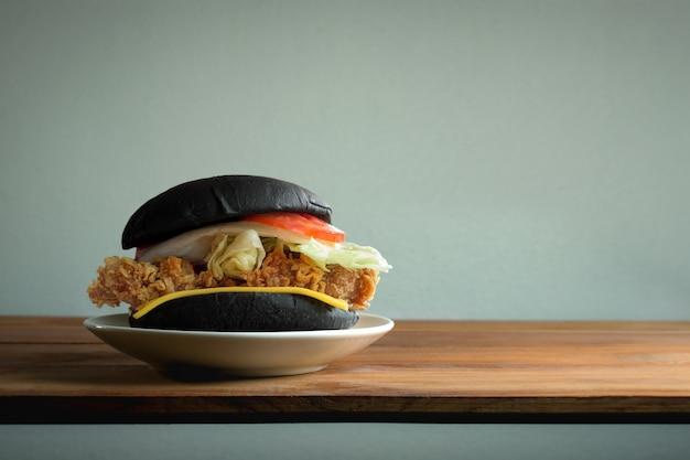 Burger de poulet classique noir sur une table en bois avec espace copie et fond de mur blanc.