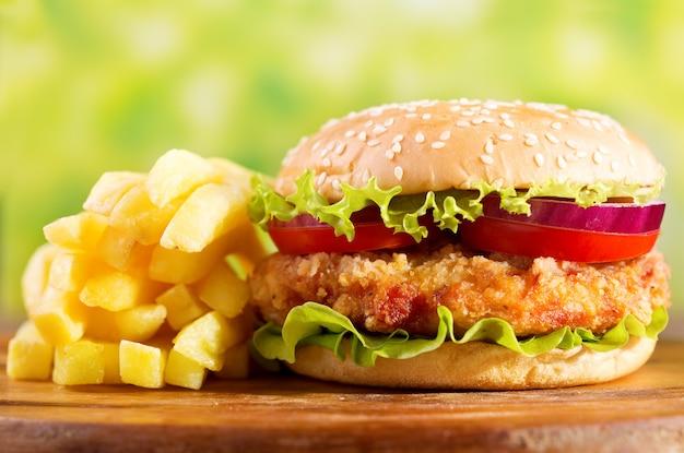 Burger de poulet avec frites sur planche de bois