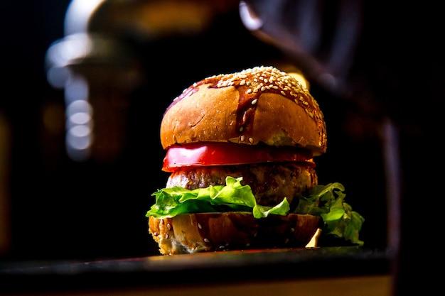Burger de poulet sur planche de bois vue côté laitue tomate