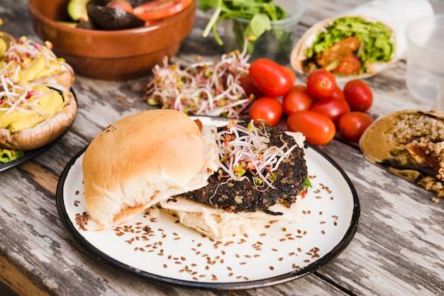 Burger de quinoa aux légumes avec des pousses et des graines de lin sur une plaque blanche