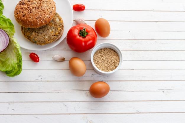 Burger de quinoa végétarien à la tomate, pain de hamburger, bol de quinoa, oignon, laitue sur un plat de fond blanc en bois avec espace de copie.