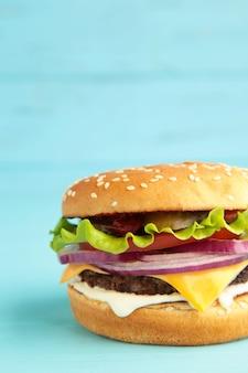 Burger savoureux frais sur bois bleu. vue de dessus. photo verticale