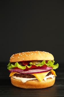 Burger savoureux frais sur noir. vue de dessus. photo verticale