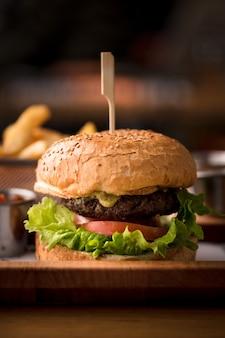 Burger savoureux frais sur table en bois