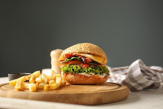 Burger savoureux avec frites sur planche de bois