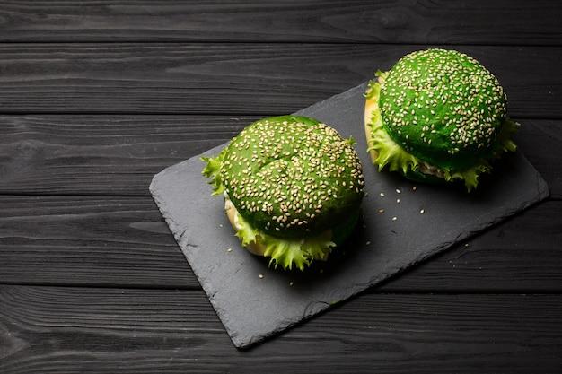 Burger savoureux vert frais sur fond noir