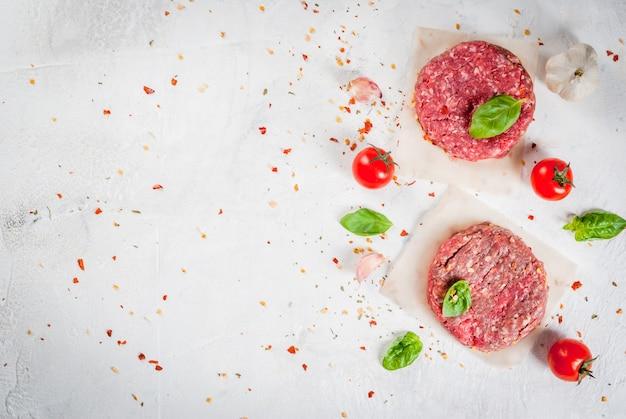 Burger de steak de boeuf haché cru frais fait maison avec des épices, des tomates et du basilic, sur une table en béton de pierre blanche, vue de dessus